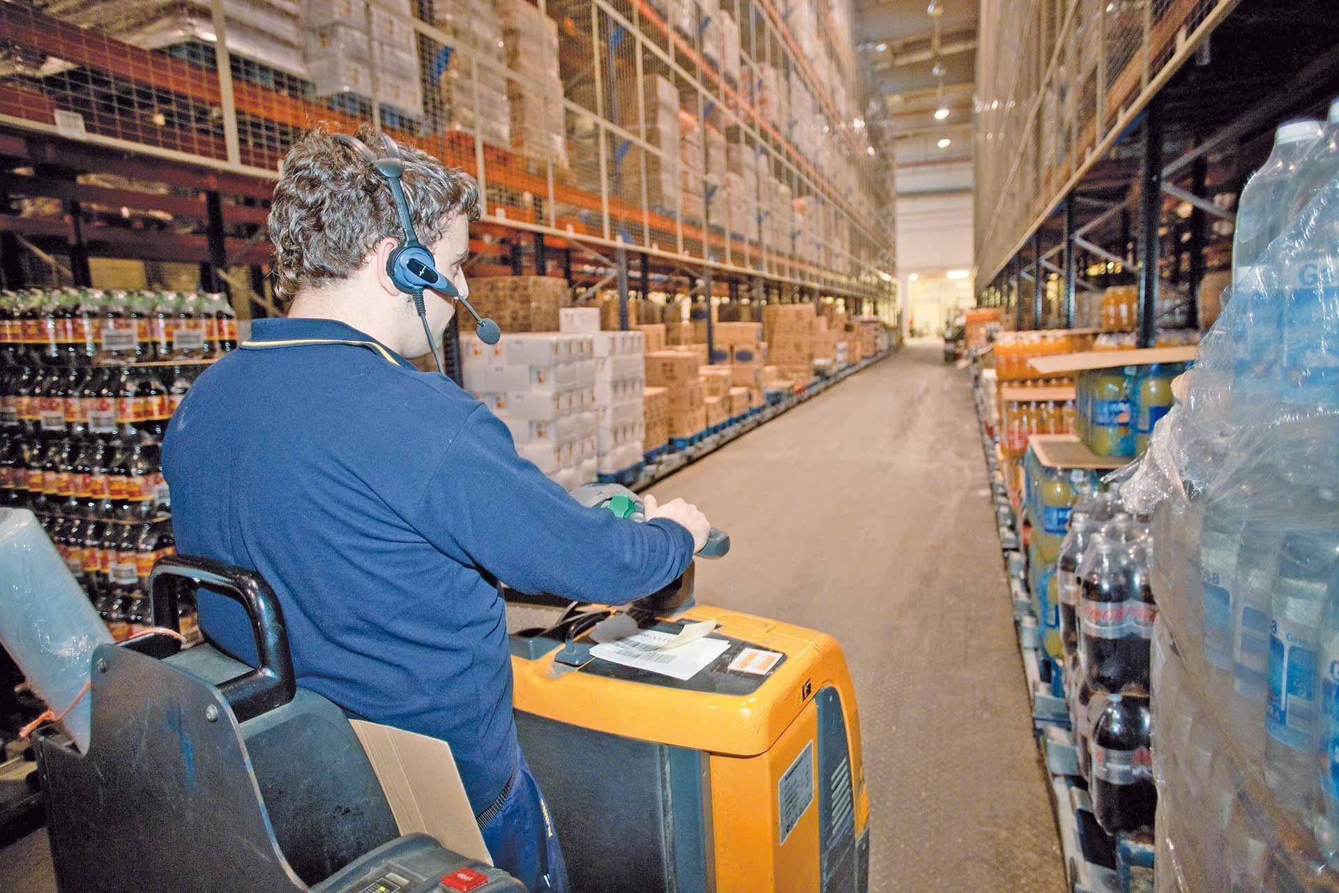 Un operario prepara pedidos en cajas asistido por un sistema de picking por voz